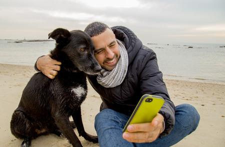 スマート フォンを使って selfie イメージを作る彼の犬を助ける男 写真素材 - 41499087