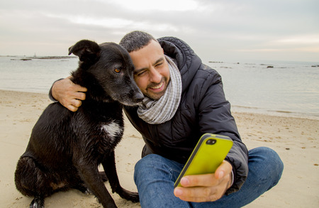 perros graciosos: Hombre ayudar a su perro haciendo selfie imagen usando un teléfono inteligente