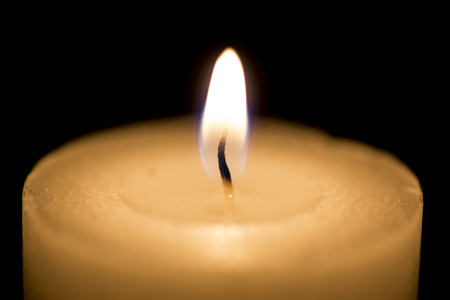 tranquil atmosphere: White thick candle with small flame on black Stock Photo