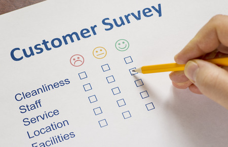 dissatisfaction: Man completing a customer survey with check boxes selecting to show his dissatisfaction at the service offered Stock Photo