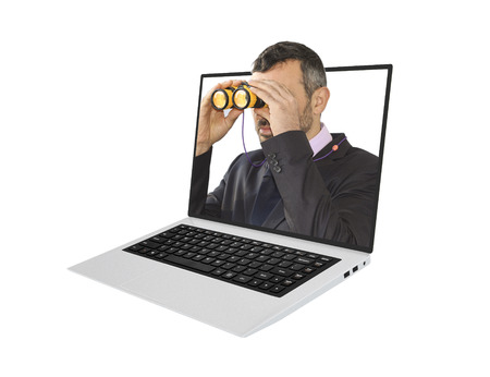 economic forecast: Online economic forecast concept. Man in suit holding binoculars inside a laptop. Stock Photo