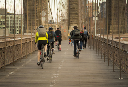 People ride thier bikes on Brooklyn Bridge Afternoon photo