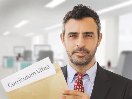 puesto de trabajo: Hombre dentro de una oficina que sostiene los papeles CV y ??los documentos de solicitud de empleo Foto de archivo
