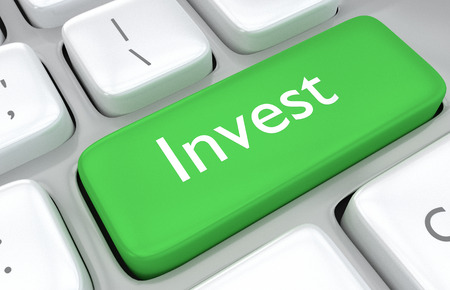 Investment concept with a close up view of a green key on a computer keyboard with the word - Invest - in white text for financial or economic themed ideas