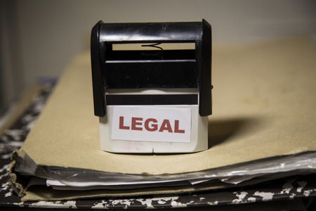 legal court: Legal word on a stamp on a big folder of paperwork Stock Photo