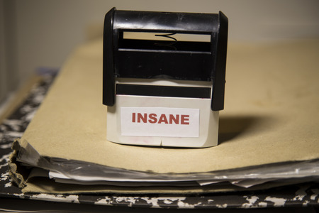 insane insanity: Officially insane stamp on a folder filles with documents