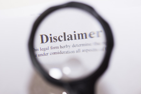 security symbol: Disclaimer written on document through magnifying glass