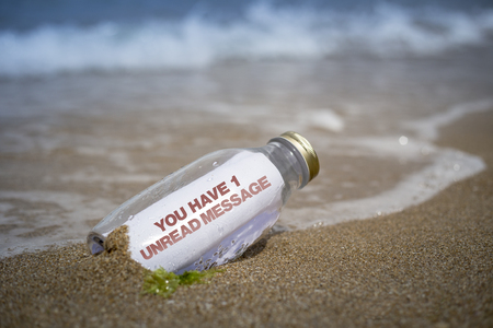 message: One unread message notice written as massage in a bottle washed ashore and layed on the sand