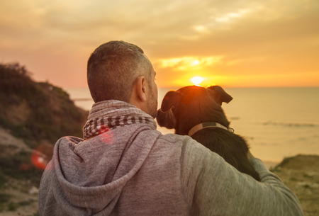 Rear view of a man cuddling his faithful dog enjoying a tranquil tropical ocean sunset with colorful orange sky with lens flare from the sun