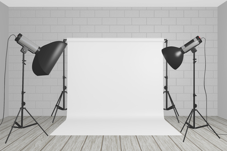Professional studio lighting set up with a white background suspended from stands, a large rectangular soft box and flashlight in a neutral white room with low ceiling and wood floor