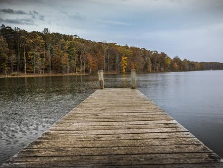 Holzbrücke auf einem See in Maryland, später Nachmittag an einem Herbsttag mit Bäumen in den warmen Farben am Hintergrund Standard-Bild - 90601650