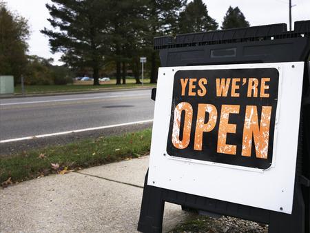 Ja, we zijn open teken geplaatst op een stoep in de buurt van de weg. Tekens om potentiële klanten aan te moedigen om in de winkel te winkelen, zijn verspreid over kleine steden.