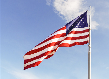 Huge US flag on a pole on a bright day