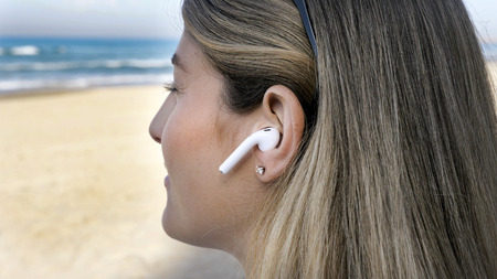 Young woman on the beach hearing music using wireless bluetooth earphones