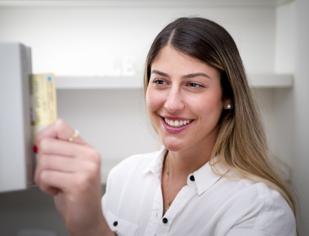 Smiling attractive woman with long blond hair inserting a credit or access card into a machine with focus to her face in a close up indoors head and shoulders portrait