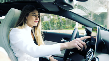 Attractive female driver operating the touchscreen on the dashboard in her car inputting data before commencing to drive viewed from inside the vehicle