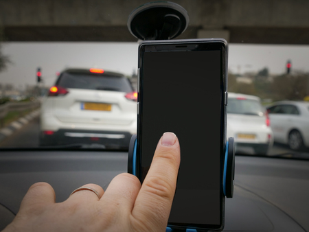 Person using a mobil while driving in traffic on a motorway in a close up view of a finger touching the blank black screen with vehicles visible behind