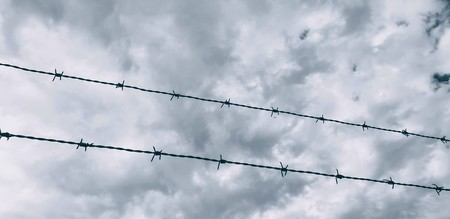 Barbwires fence over cloudy Sky background