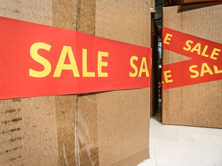 Boxes with red sale sticker in storage shelf of a store Imagens