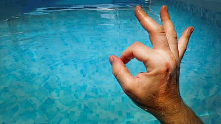 Satisfaction with ok hand gesture over swimming pool blue water background