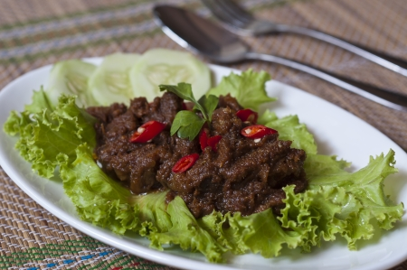 spicy beef rendang with cucumber and salad
