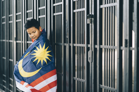 Kid showing or holding a Malaysian flag (selective focus) 写真素材
