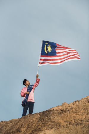 Photo of a boy dressing in a traditional clothes is holding the malaysian flag to celebrate Malaysia's independence day Stock Photo