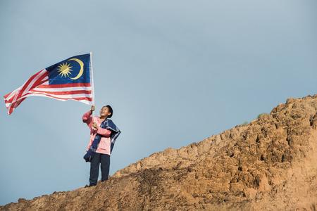 De foto van een jongen die zich in traditionele kleren kleden houdt de Maleise vlag om de onafhankelijkheidsdag van Maleisië te vieren Stockfoto