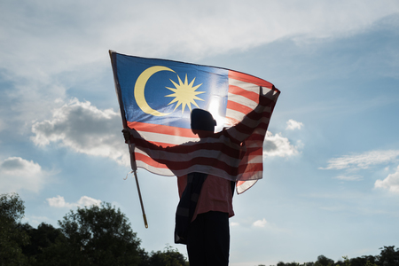 Silhouette of a boy holding the malaysian flag celebrating the Malaysia independence day 스톡 콘텐츠