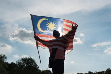 Silhouet van een jongen die de Maleise vlag houdt die de onafhankelijkheidsdag van Maleisië viert