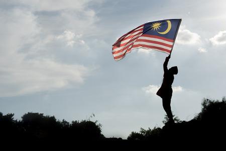 マレーシア独立記念日を祝うマレーシアの旗を握る少年のシルエット