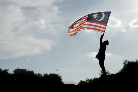 Silhouette of a boy holding the malaysian flag celebrating the Malaysia independence day Фото со стока