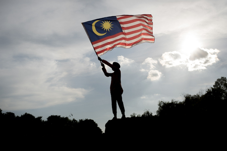 말레이시아 독립 기념일을 축하하는 말레이시아 국기를 들고 소년의 실루엣