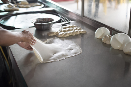 preparing,frying,cooking or making the malaysian flatbread,also known as roti canai.famous and popular in asia,especially malaysia.breakfast,lunch and dinner meal.famous food in malaysia