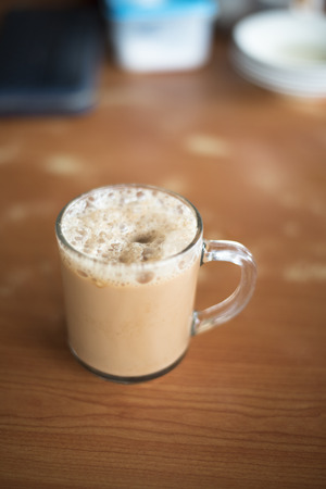 kopitiam: a glass of tea with milk on a table at mamak restaurant.famous or popular drink in malaysia.Malaysian favorite drink known as Teh Tarik.signature menu at mamak stall,cafe,restaurant or bistro