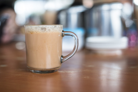 a glass of tea with milk on a table at mamak restaurant.famous or popular drink in malaysia.Malaysian favorite drink known as Teh Tarik.signature menu at mamak stall,cafe,restaurant or bistro Фото со стока - 85317671