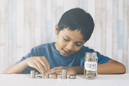 young boy counting his coinssavings to buy dream toys. Saving concept