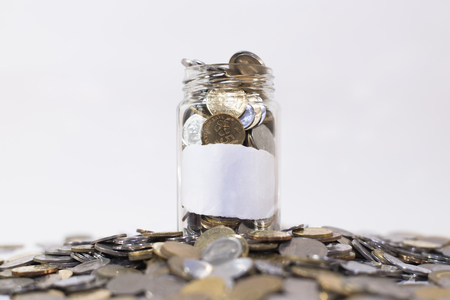 Glass jar filled with coins on a group of coins.attached with empty white paper. isolated on white background. financial concept. malaysia currency