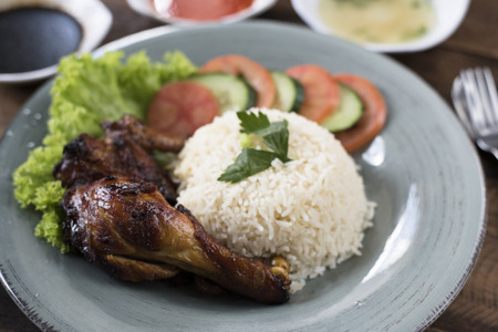 Popular Malaysian dish Nasi Ayam or chicken rice with baked chicken pieces, tomato, cucumber, salad, soup, soy sauce and chili sauce.