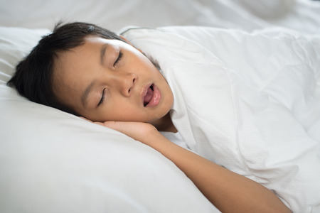 young boy sleeping with mouth open (snoring) on bed white pillow and sheet.boy asleep and snoring.sleep concept Stock Photo