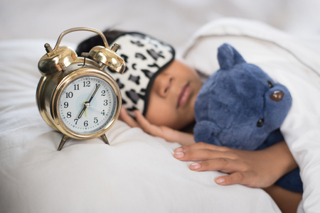 asian boy sleeping on bed white pillow and sheet with alarm clock and teddy bear.boy sleeping in morning wearing sleep mask Фото со стока - 89988457