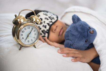 Niño asiático durmiendo en la cama almohada blanca y hoja con reloj despertador y osito de peluche. niño durmiendo en la mañana con máscara de dormir Foto de archivo - 89988457