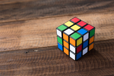 colorful rubik's cube on a wooden table background.braint teaser toy