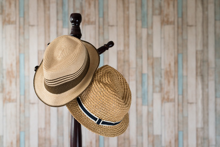 Straw hat hanging on wooden hanger.clothing accessories and travel concept Foto de archivo