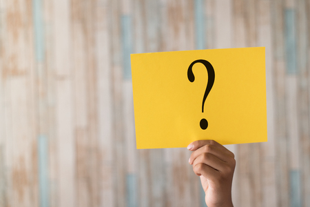 hand holding a paper note with question mark.question mark written on paper Stock Photo