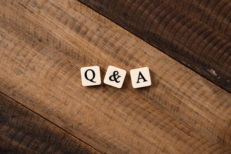 質疑応答 Q&A の概念。木製テーブル上のアルファベットタイル上のQ&Aレター
