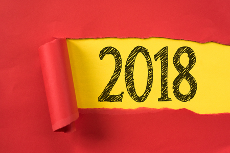 Torn piece of red paper uncovering 2018 underneath. new year concept.