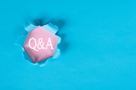 Blue torn paper with revealing Q&A word. Questions and Answers concept background. Stock Photo
