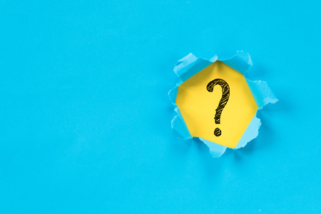 blue torn paper revealing question mark symbol on yellow paper. question mark background.