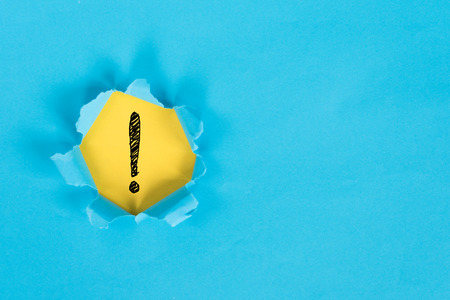 blue torn paper revealing exclamation mark on yellow paper. exclamation mark background concept. Stock Photo